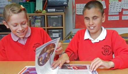 a braille-reading student and a sighted student sharing a book in the classroom